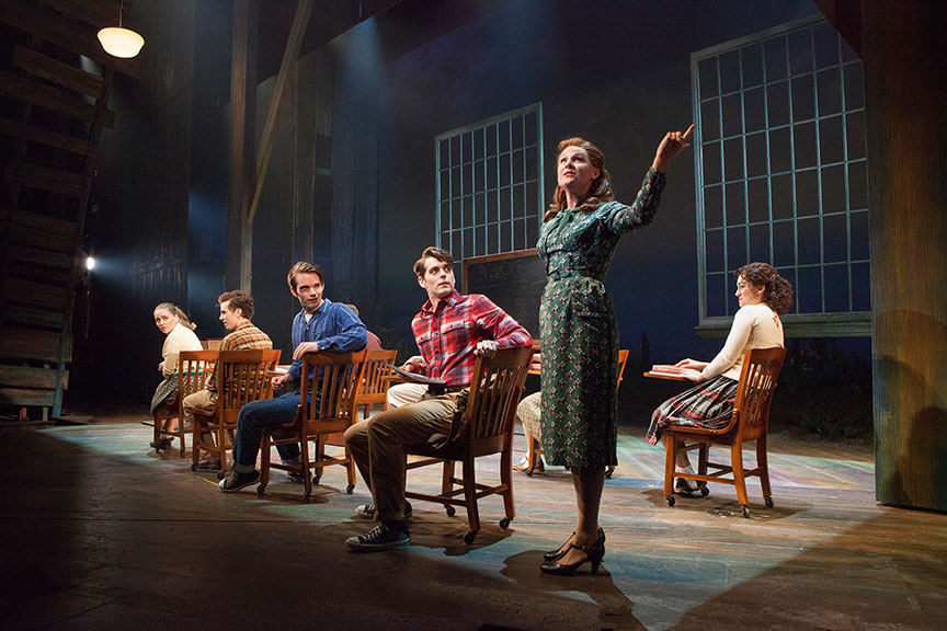 (foreground) Sandra DeNise as Miss Riley with the cast of the West Coast premiere of October Sky, with book by Brian Hill and Aaron Thielen, music and lyrics by Michael Mahler, directed and choreographed by Rachel Rockwell, inspired by the Universal Pictures film and Rocket Boys by Homer H. Hickam, Jr., running Sept. 10 - Oct. 23, 2016 at The Old Globe. Photo by Jim Cox.