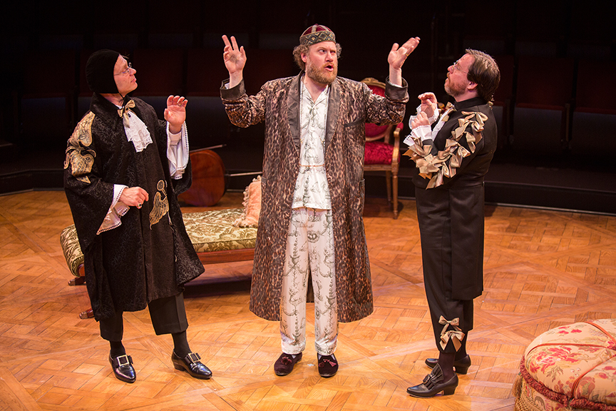 (from left) Noah Brody appears as Dr. Diafoirus, Andy Grotelueschen as Argan, and Paul L. Coffey as Thomas Diafoirus in the world premiere adaptation of Molière's The Imaginary Invalid, adapted by Fiasco Theater, running May 27 – June 25, 2017 at The Old Globe. Photo by Jim Cox.
