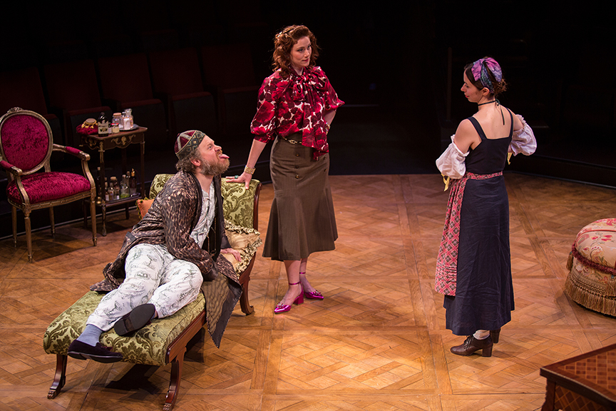 (from left) Andy Grotelueschen appears as Argan, Jessie Austrian as Béline, and Emily Young as Toinette in the world premiere adaptation of Molière's The Imaginary Invalid, adapted by Fiasco Theater, running May 27 – June 25, 2017 at The Old Globe. Photo by Jim Cox.