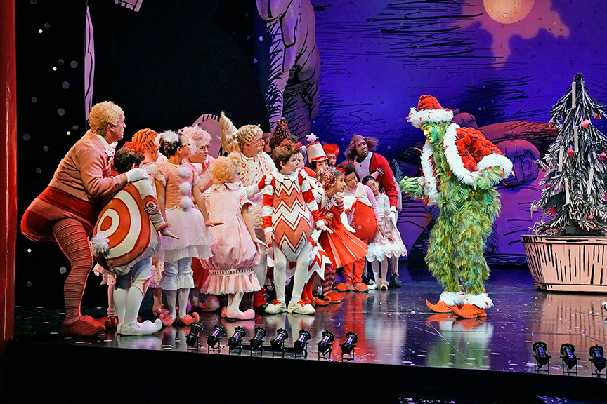 (far right) Edward Watts appears as The Grinch with the cast of Dr. Seuss's How the Grinch Stole Christmas!, book and lyrics by Timothy Mason, music by Mel Marvin, original production conceived and directed by Jack O'Brien, original choreography by John DeLuca, and directed by James Vásquez, running November 3 – December 29, 2018 at The Old Globe. Photo by Ken Howard.