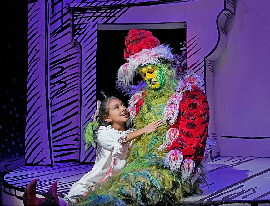 Leila Manuel appears as Cindy-Lou Who and Edward Watts as The Grinch in Dr. Seuss's How the Grinch Stole Christmas!, 2018. Book and lyrics by Timothy Mason, music by Mel Marvin, original production conceived and directed by Jack O'Brien, original choreography by John DeLuca, and directed by James Vásquez, running November 10 – December 29, 2019 at The Old Globe. Photo by Ken Howard.